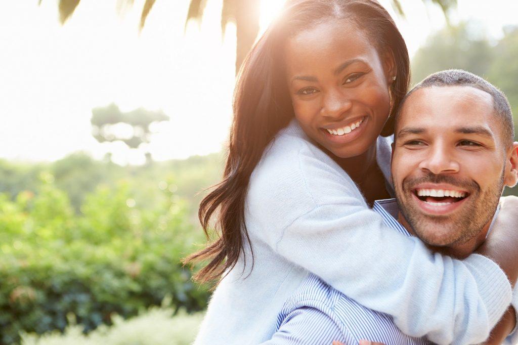 Imagem de um lindo casal afrodescendente, ambos estão lindos, risonhos e felizes.