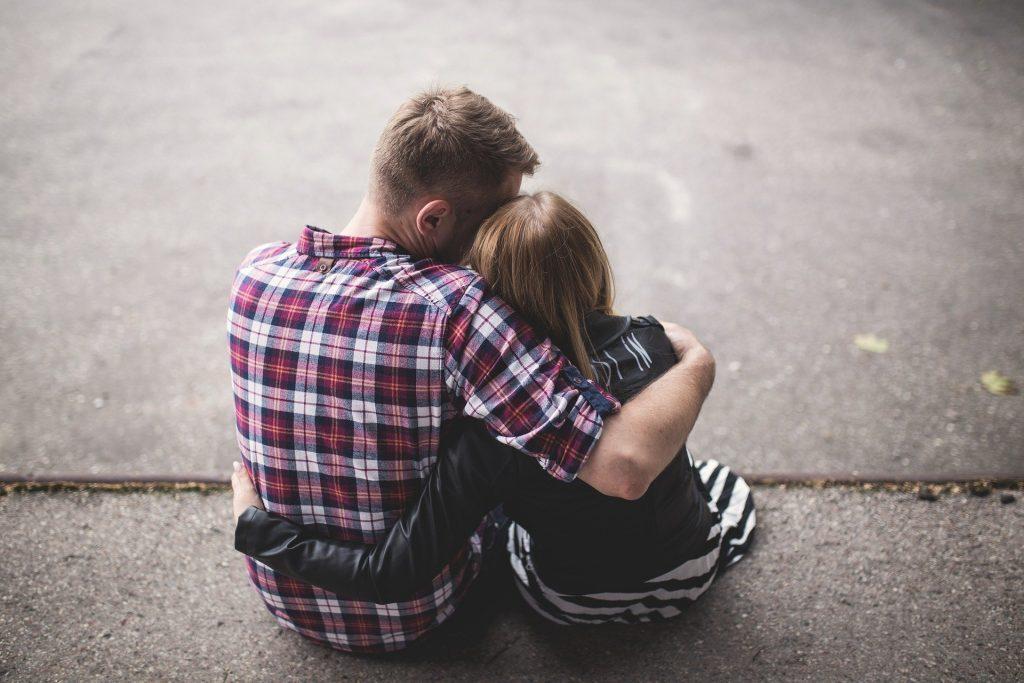 Imagem de um casal abraçados e sentados no chão. Ele usa uma camisa xadrez nas cores vermelho, azul e branco e ela usa um vestido listrado nas cores preto e branco e uma jaqueta na cor preta sobre ele.