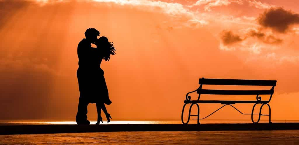 Imagem de fundo alaranjada e em destaque a silhueta de um casal se beijando. Ao lado deles um banco estilo de praça feito de ferro.