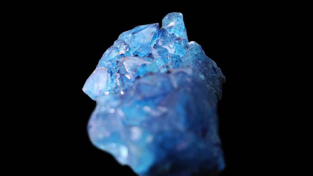 Imagem de fundo preto e em destaque um lindo cristal de água-marinha na cor azul.