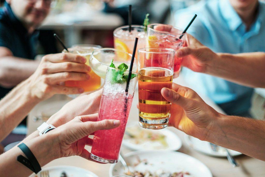 Imagem de várias mãos segurando copos com drinks bem coloridos. Os copos estão decorado e cada um tem um canudo e e alguns possuem uma folha de hortelã.