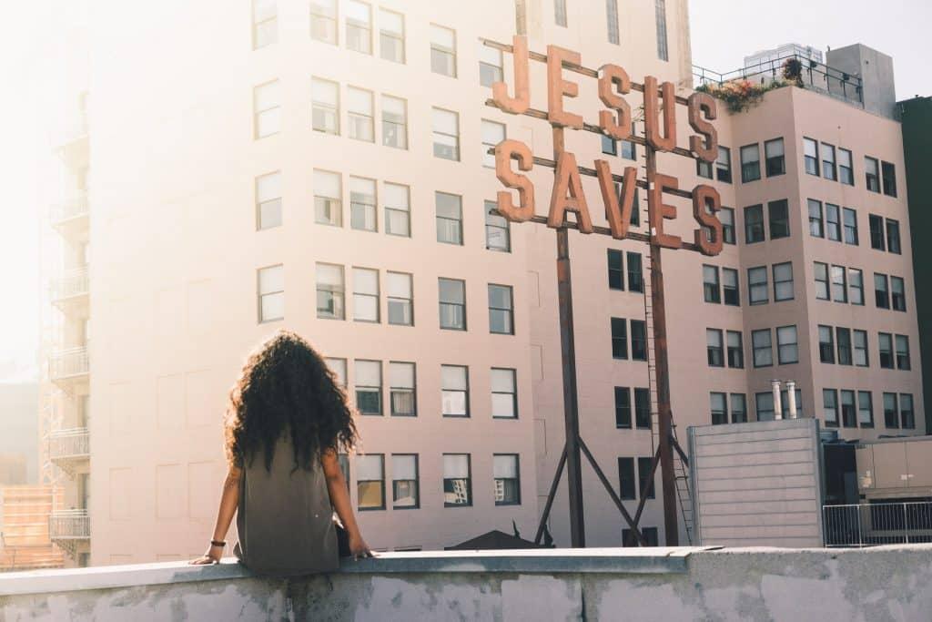 Mulher negra de costas sentada no parapeito de um prédio.