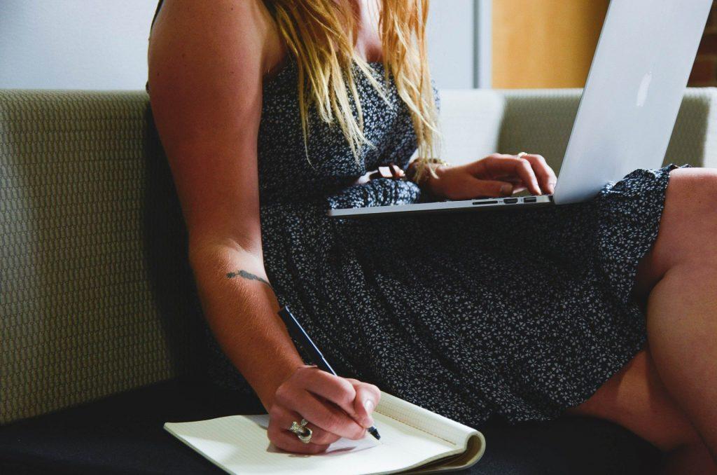 Imagem de uma mulher de cabelos ruivos e longos usando um vestido fresquinho. Ela está sentada em um sofá bege e com um notebook sobre o seu colo. Uma das mãos segura  uma caneta e ela escreve em um caderno que está ao lado dela.