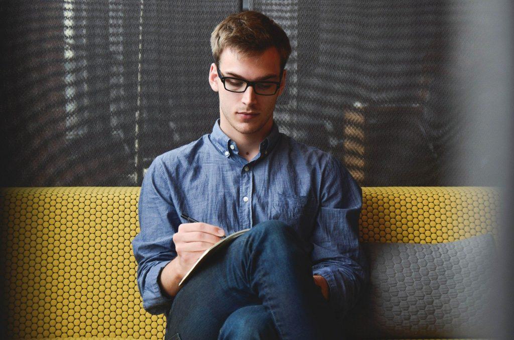 Imagem de um jovem sentado em um sofá de fundo amarelo, ao lado uma almofada cinza. Ele usa camisa e calça jeans, um óculos de grau. Sobre a sua perna um caderno e ele está fazendo algumas anotações com uma caneta.