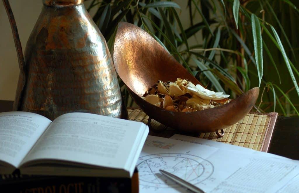 Imagem de uma mesa e sobre ela um livro aberto, algumas folhas com o desenho de um mapa astral. Ao lado um vaso com folhagem verde, um menor com flores e seda na cor bege e uma jarra de bronze.