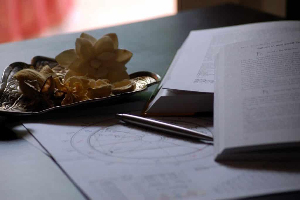 Imagem de uma mesa branca e sobre ela alguns papéis onde estão sendo desenhados um mapa astral, dois livros de estudos e um porta-peso de bronze com algumas flores na cor bege.