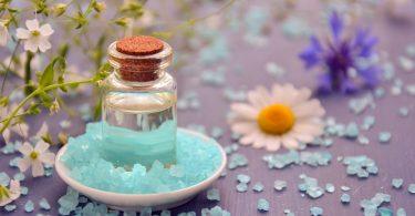 Imagem de um pequeno frasco de vidro contendo óleo essencial. Ele está disposto em um pires branco de porcelana sobre uma mesa decoarada com flores e cristais azul.