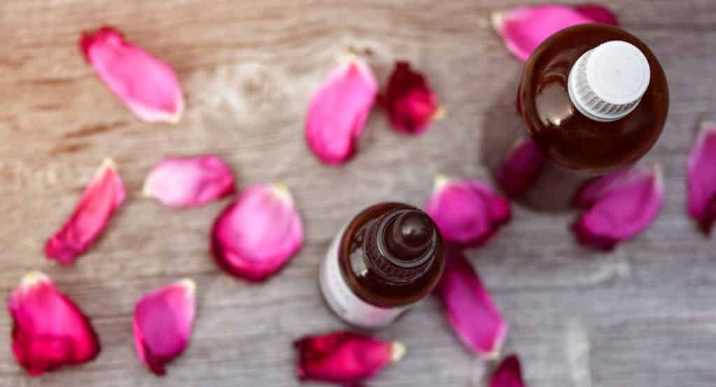 Imagem de dois frascos de vidro marrom contendo óleo essencial. Eles estão dispostos sobre uma mesa de madeira decorada com pétalas de rosas na cor rosa.