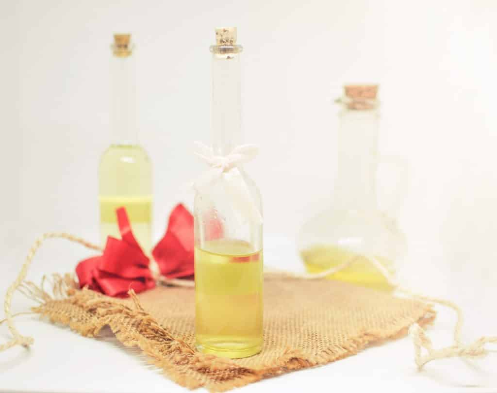 Imagem de vários frascos de vidro de formatos diferentes contendo óleo essencial. Eles estão sobre um pedaço de juta decorado com um laço de fita na cor vermelho.