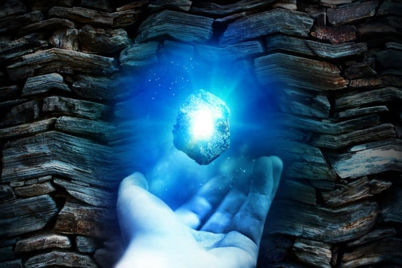 Imagem com um fundo de pedras e em destaque a mão de um homem segurando um cristal de água marinha que emana uma luz muito forte na cor azul.