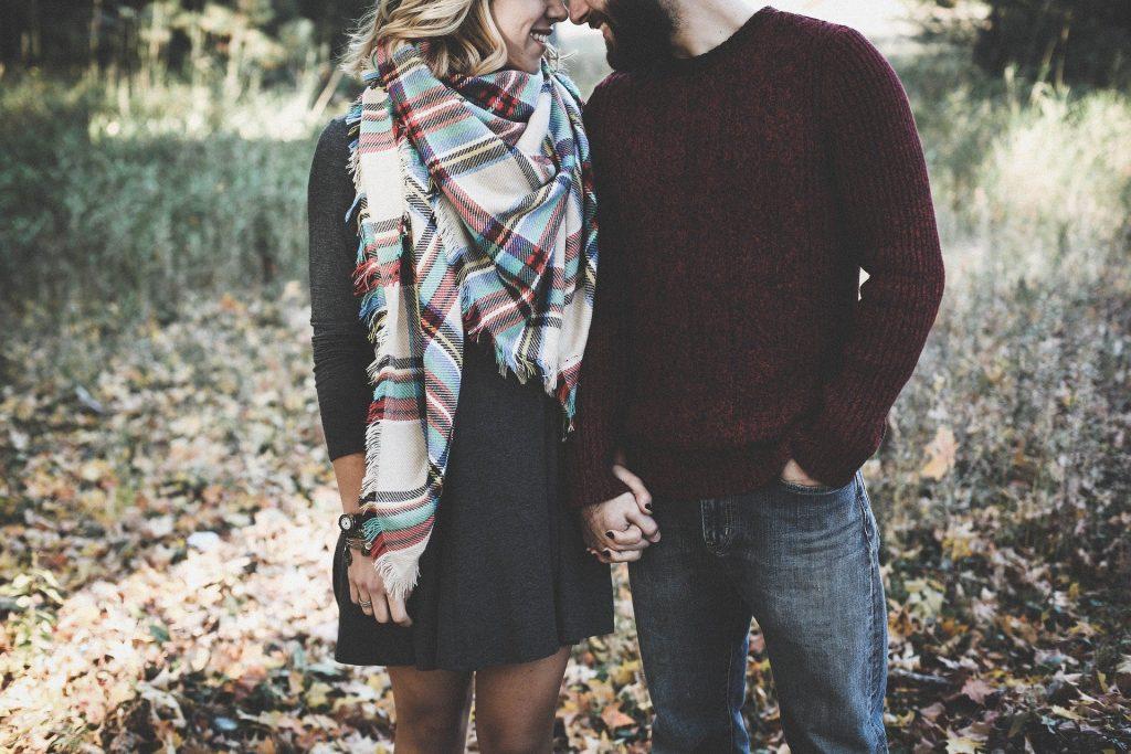 Imagem de um casal, um ao lado do outro e de mãos dadas. Ela usa um vestido cinza e um chalé quadriculado no pescoço. Ele usa uma calça jeans e uma blusa de lã na cor vinho. Ambos estão se olhando apaixonados.