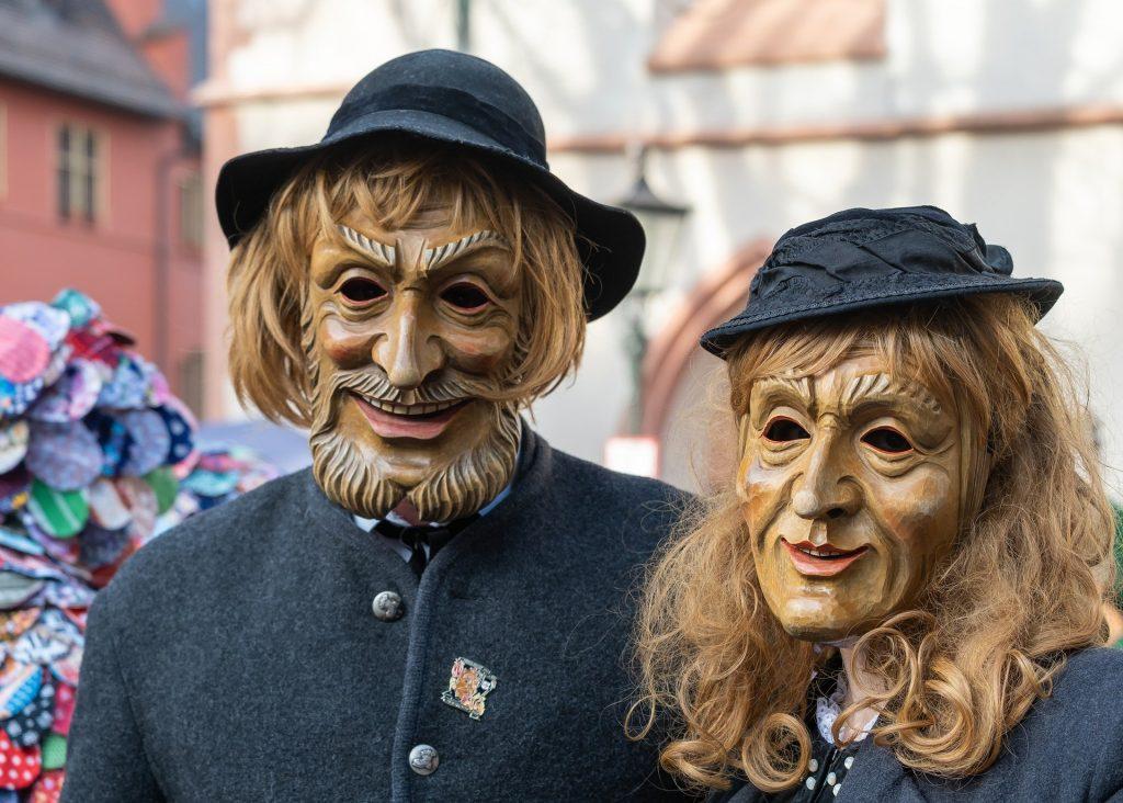 Imagem de um casal, homem e mulher, usando máscara de carnaval de uma série.  Ambos estão na rua, curtindo a festa.