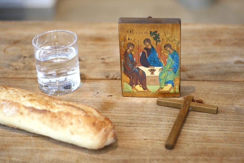 Imagem com um quadro pequeno de jesus, um cruz, um copo com água e um pedaço de pão, simbolizando o jejum durante a quaresma.