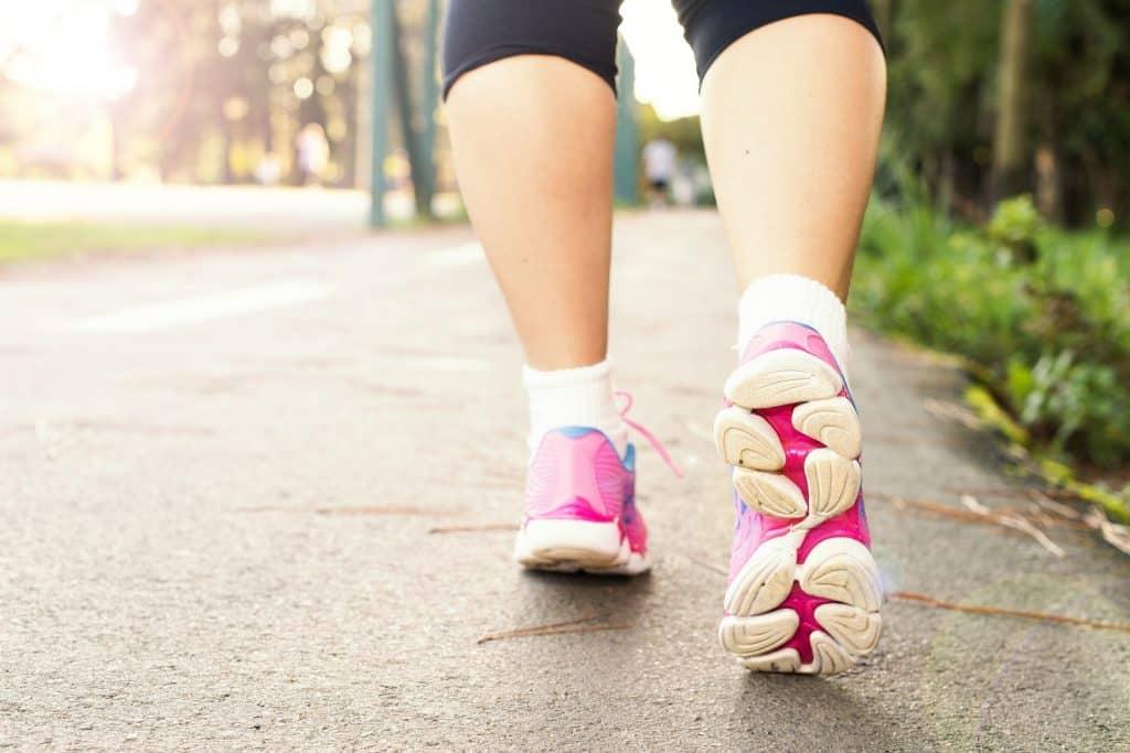 Imagem das pernas de uma mulher que está caminhando. Ela usa um tênis na cor rosa e uma calça legging na cor preta.