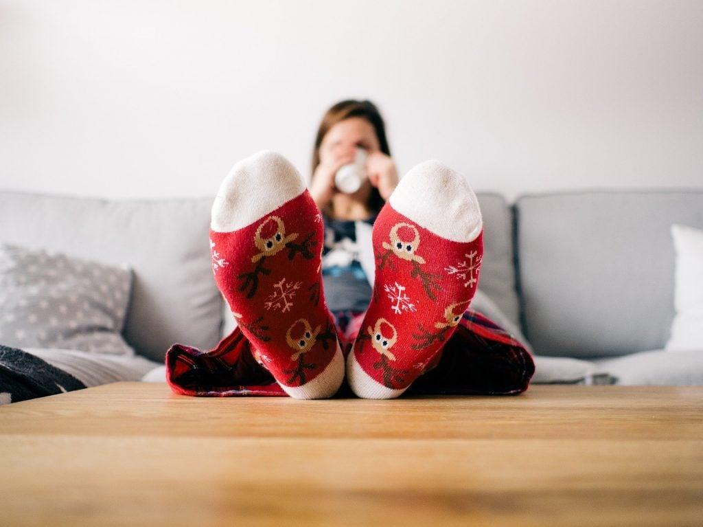 Imagem de uma mulher em sua sala de estar. Ela está descansando sentada em seu sofá cinza. Ela está com os pés sobre uma mesa aparadora de madeira e degusta um saboroso café em uma xícara de porcelana na cor branca. O destaque são para as meias dela: vermelha e com vários desenhos de uma carinha da rena.