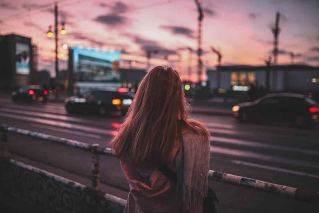 Mulher de costas numa avenida com carros.