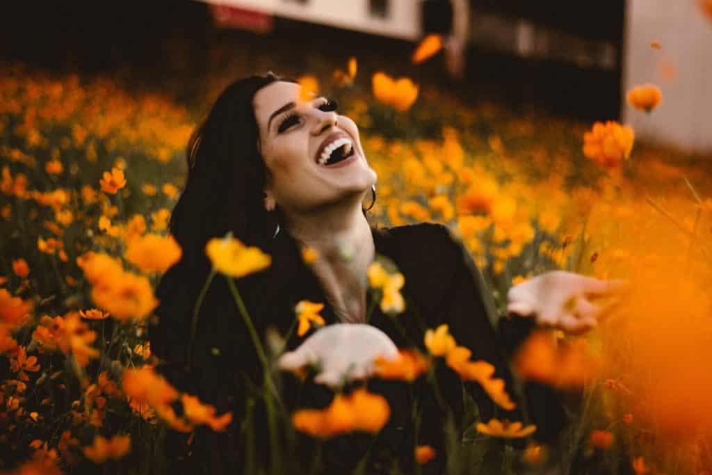 Imagem de um lindo campo florido de cor alaranjada. No centro desse campo, uma linda moça de cabelos longos e escuro sorrindo e com as mãos abertas em sinal de gratidão.
