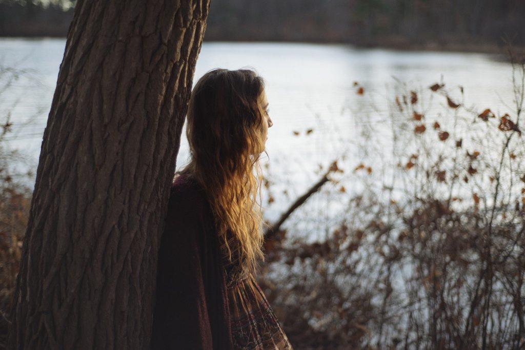 Imagem de fundo contendo um lindo lago. Em destaque uma moça de cabelos longos encostada em uma árvore, ela está pensativa e olhando para o lago.