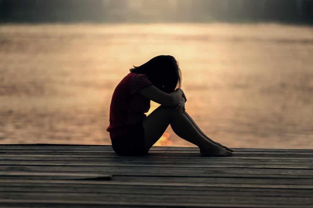 Imagem de uma garota usando shorts e camiseta sentada no chão de um pier e na frente do mar. Ela está triste, com a cabeça baixa.