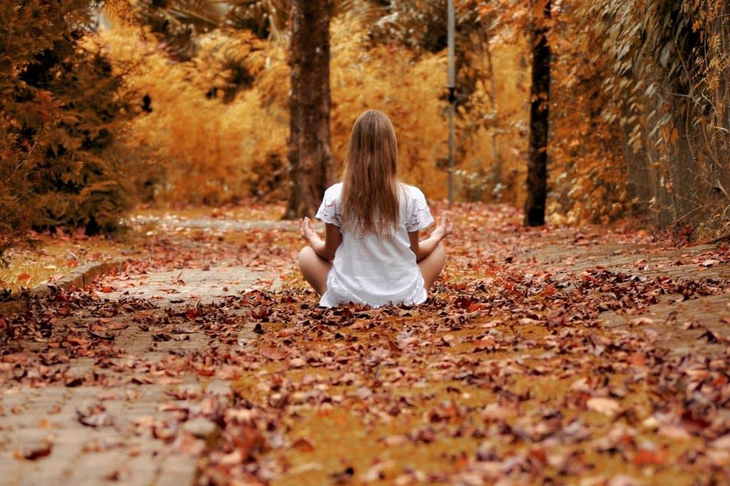 Imagem de uma moça sentada em um chão forrado de folhas. Ela está praticando a meditação.
