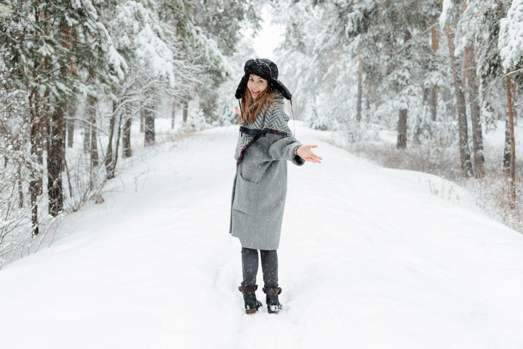 Imagem de uma mulher caminhando em um parque todo coberto com neve. Ela está sorrindo e usa muitas roupas de inverno, próprias para este clima.