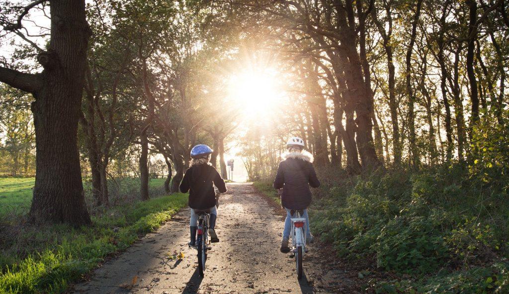 Imagem de um casal andando de bicicleta em uma rua de terra e ao lado muitas árvores. Ambos vestem calça jeans, casacos de frio na cor preto e um capacete protetor na cabeça.