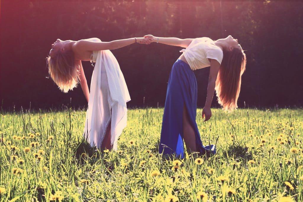 Imagem de duas garotas de mão dadas. Elas estão em um jardim gramado e florida. Ambas usam saias longas, uma na cor azul e a outra na cor branca.