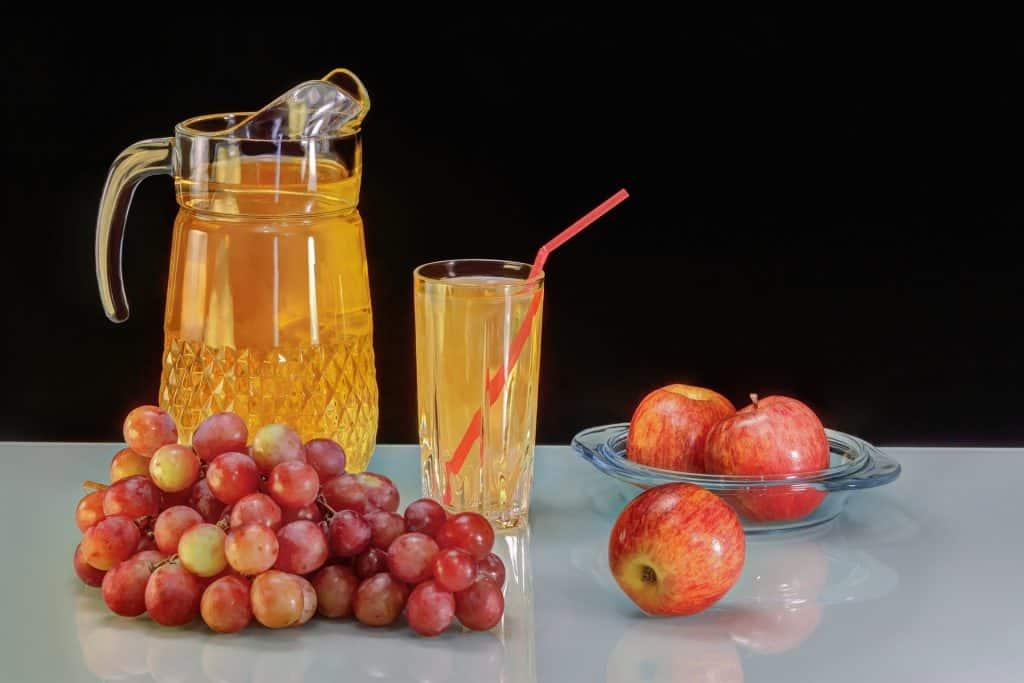 Imagem de fundo preto e em destaque uma jarra cheia de suco de maçã. Ao lado um copo contendo o mesmo suco e um canudo dentro dele. Ao lado e sobre a mesa uma tigela de vidro com duas maçãs vermelhas e ao lado da jarra um cacho de uvas vermelhas e uma maçã.