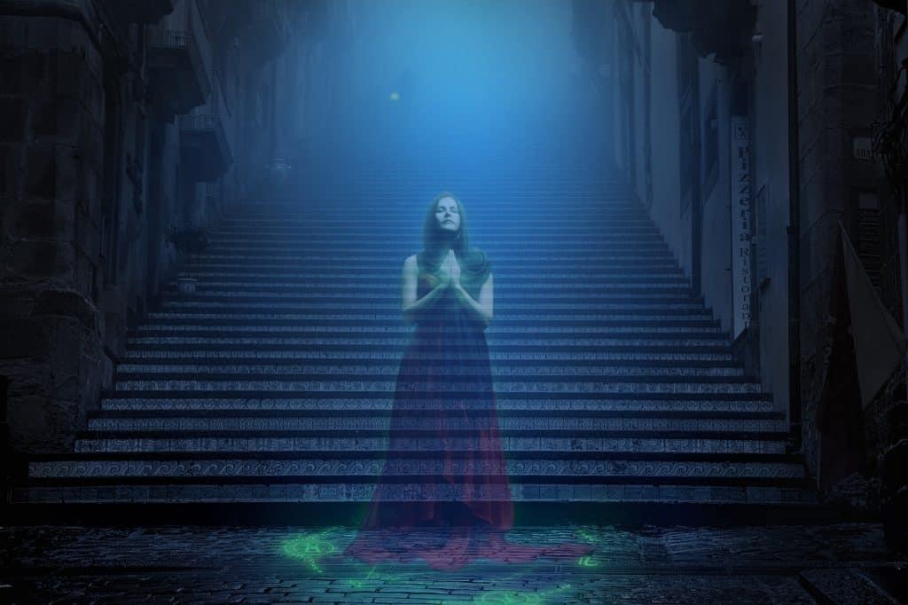 Imagem de uma assombração mulher parada no começo de uma grande e extensa escadaria. Ao fundo dela um forte luz na cor azul.