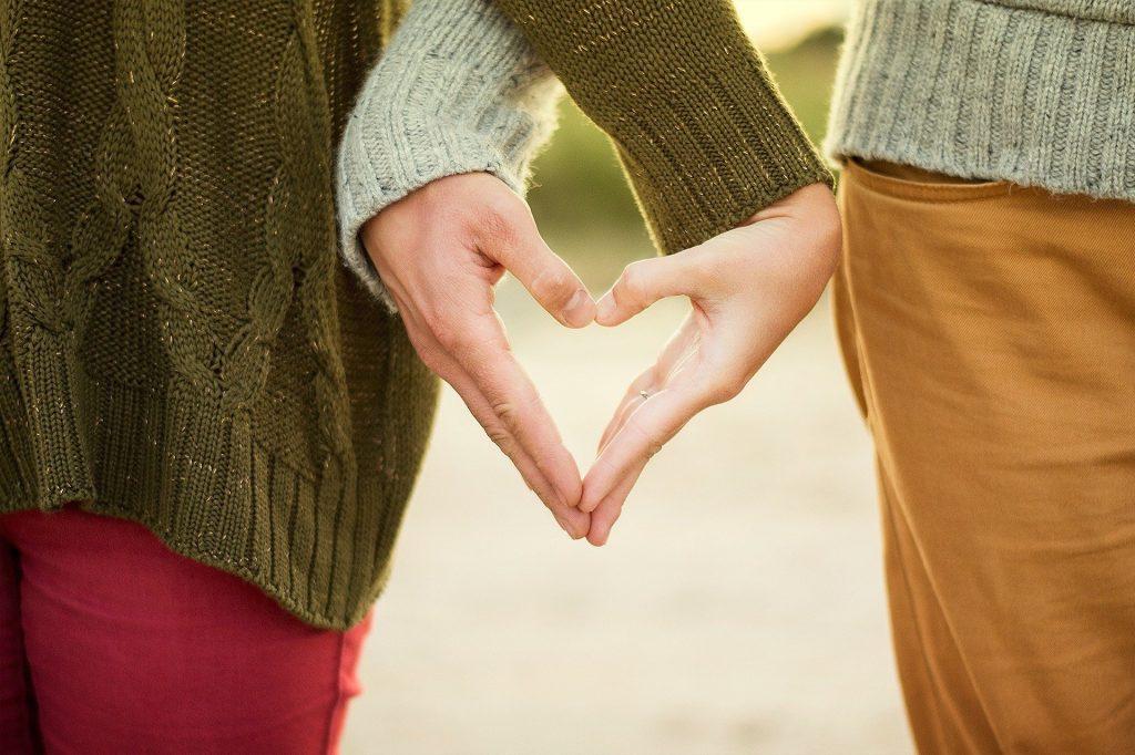 Imagem de um casal de mãos dadas formando um coração. Ela usa blusa de lã marrom e uma calça rosa. Ele usa uma blusa bege clara e uma calça bege mais escura.