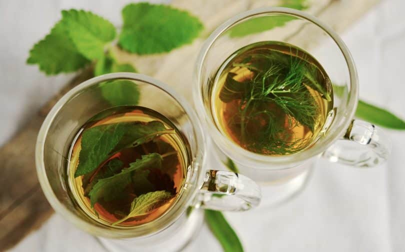 Imagem de duas canecas de vidro contendo remédios caseiros para refluxo. É um chá feito com ervas.