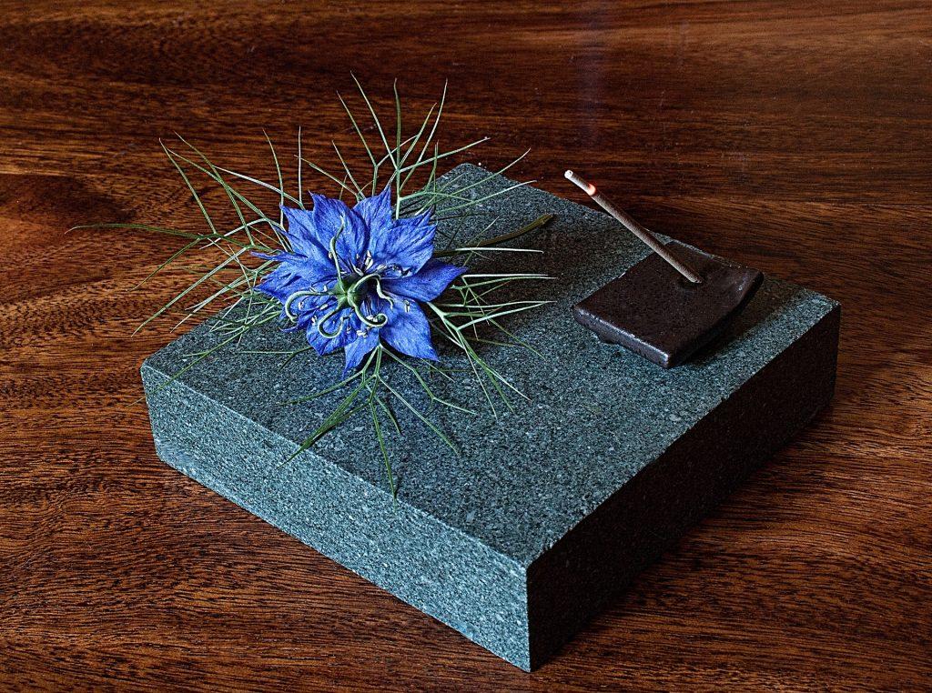 Imagem de um incenso de alecrim queimando sobre um porta incenso disponível sobre uma pedra de granito na cor cinza. Sobre essa pedr uma linda flor na cor roxa.