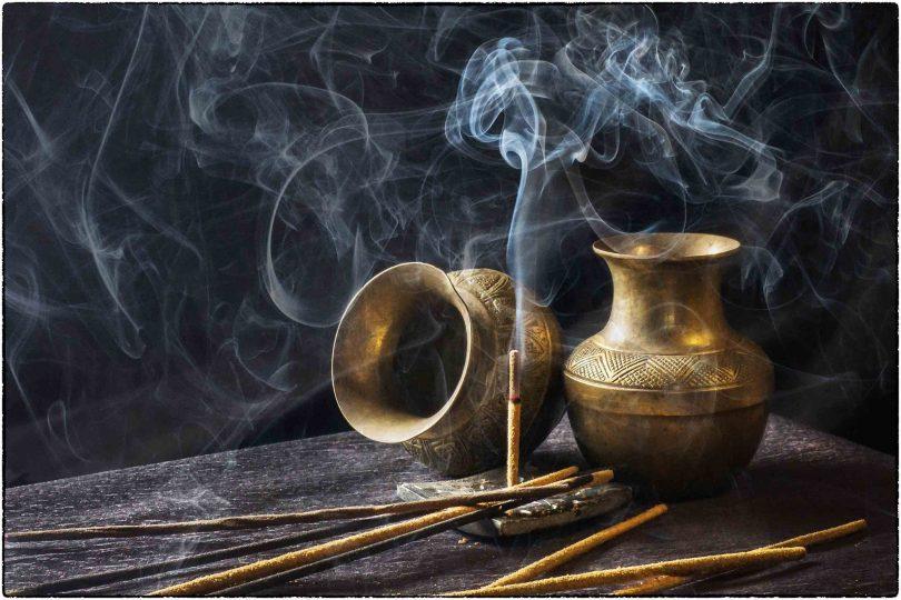 Imagem de vários incensos de alecrim dispostos sobre uma mesa de madeira. Apenas um deles está sendo queimado. Ao lado dois vasos de bronze decoram a mesa.