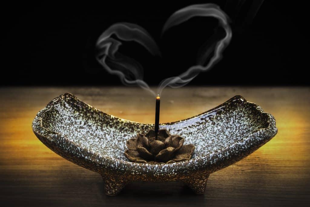 Imagem de um incenso de alecrim queimando e disposto sobre um suporte decorado com uma flor de lótus feita em bronze.