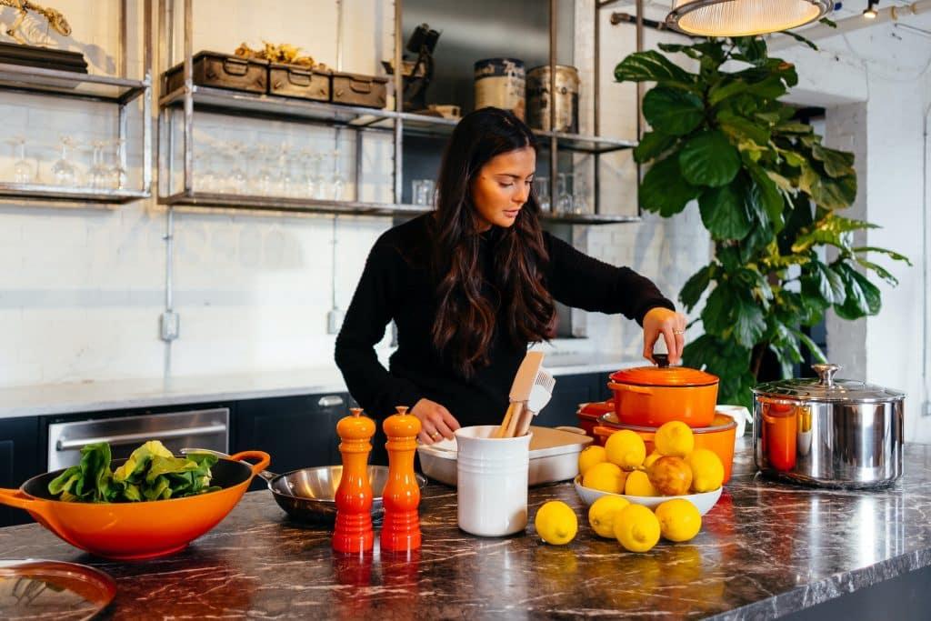 Imagem de uma cozinha e uma linda bancada de mármore. Em destaque uma mulher de cabelos longos e blusa de frio na cor preta. Ela está cozinhando. Sobre a bancada temos vários tipos e modelos de panelas na cor laranja e alguns ingredientes como verdura e limões.