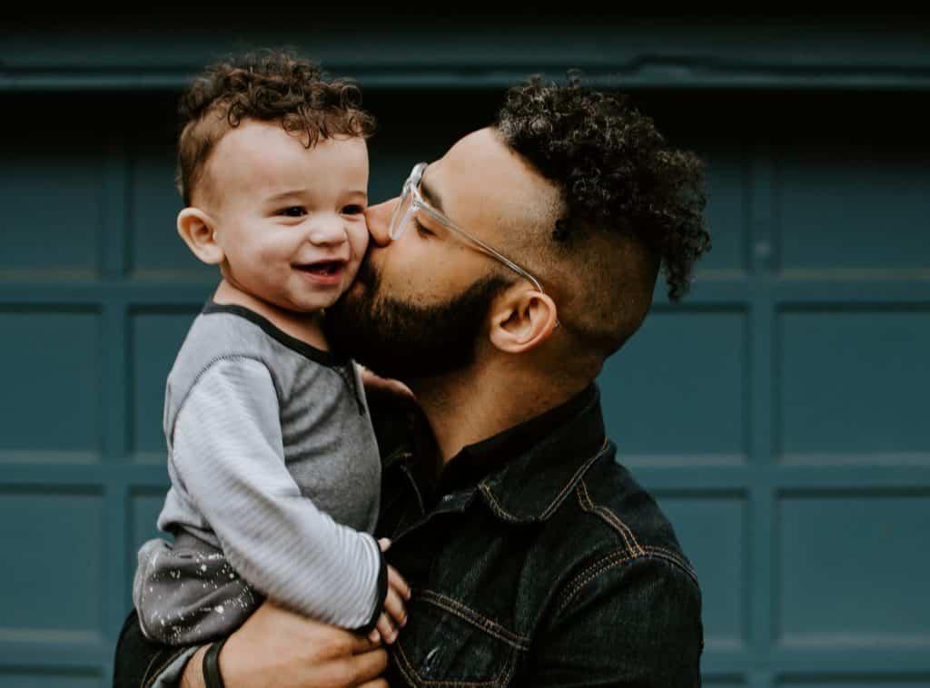 Homem dando beijo na bochecha de bebê.