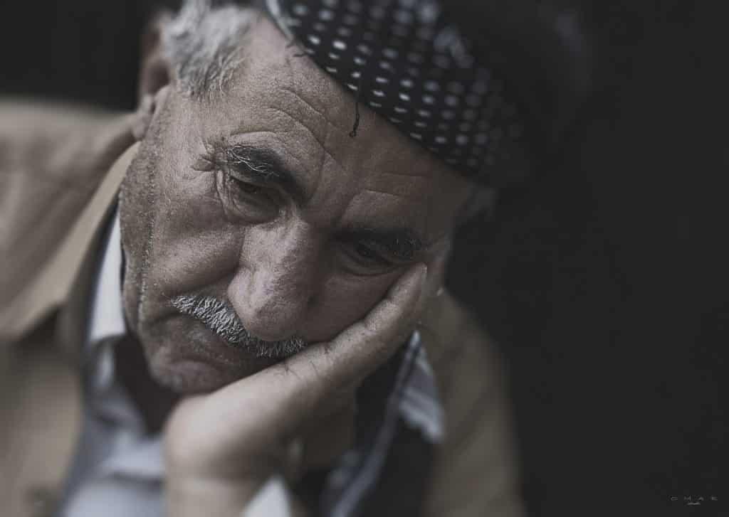 Imagem de um senhor triste, cabisbaixo. Ele está com uma de suas mãos segurando um do lado do seu rosto. Ele usa bigodes e uma boina sobre a cabeça.