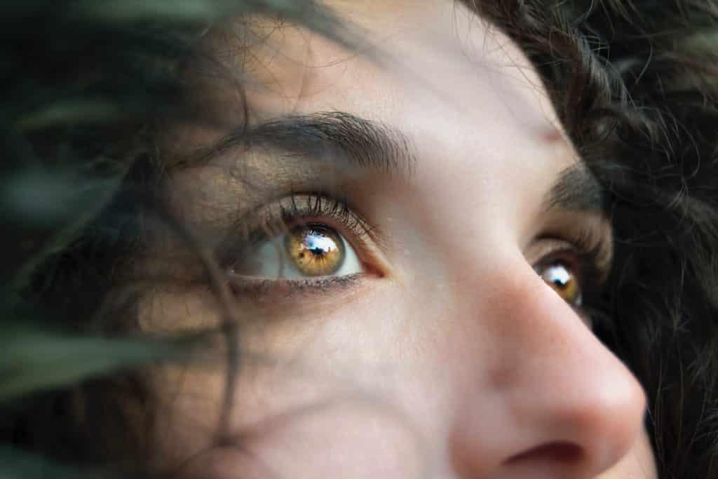 Imagem do olhar pensativo e triste de uma linda mulher de olhos castanhos claros.