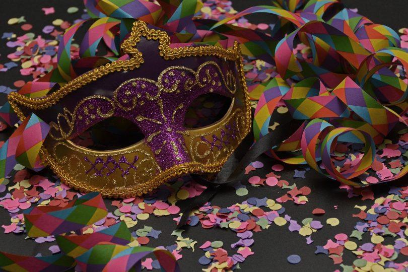 Imagem de uma máscara de carnaval nas cores dourada e roxa. Ela está sobre uma mesa de fundo preto e na mesa estãoo espalhados confetes e serpentinas coloridas.