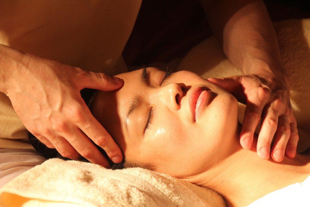 Imagem de uma mulher deitada de barriga para cima. Ela está com os olhos fechados e sobre ela uma luz. Atrás dela, um homem posiciona suas mãos sobre a testa e o rosto dela.