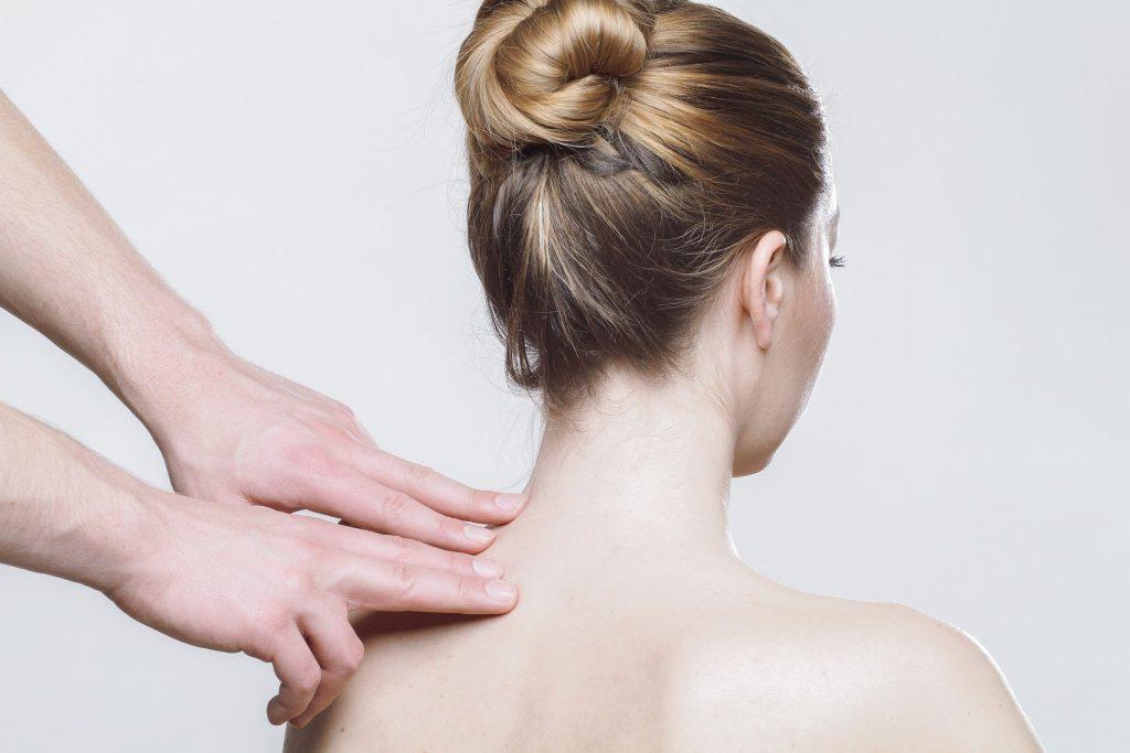 Imagem de uma mulher de cabelo preso, sentada de costas. Em pé um homem que está colocando suas mãos sobre um lado do ombro da paciente.