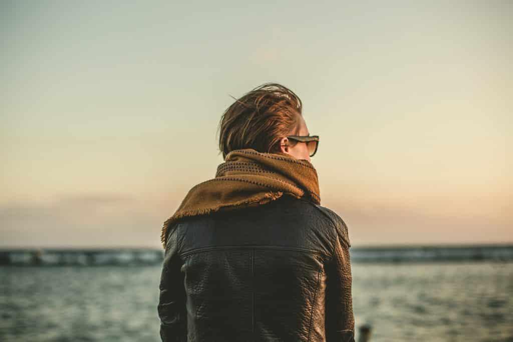 Imagem de fundo de um lindo mar e em destaque uma mulher de costas olhando pensativa para ele. Ela usa uma jaqueta de couro, cachecol marrom e um óculos de sol.