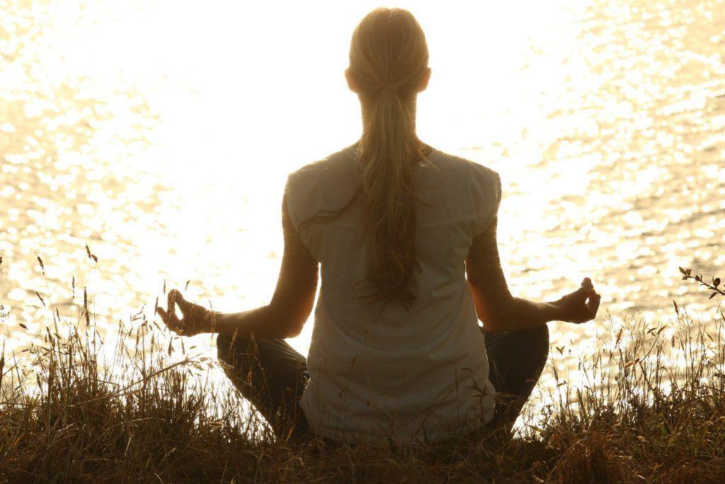 Imagem de uma mulher loira de costas praticando a meditação em frente de um rio. Ela está sentada em um gramado. Usa uma calça escura e uma camiseta branca.