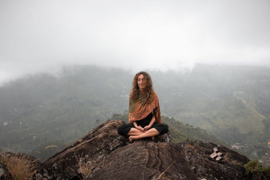 Imagem de uma montanha com neblina. Em destaque uma mulher meditando sobre uma rocha.