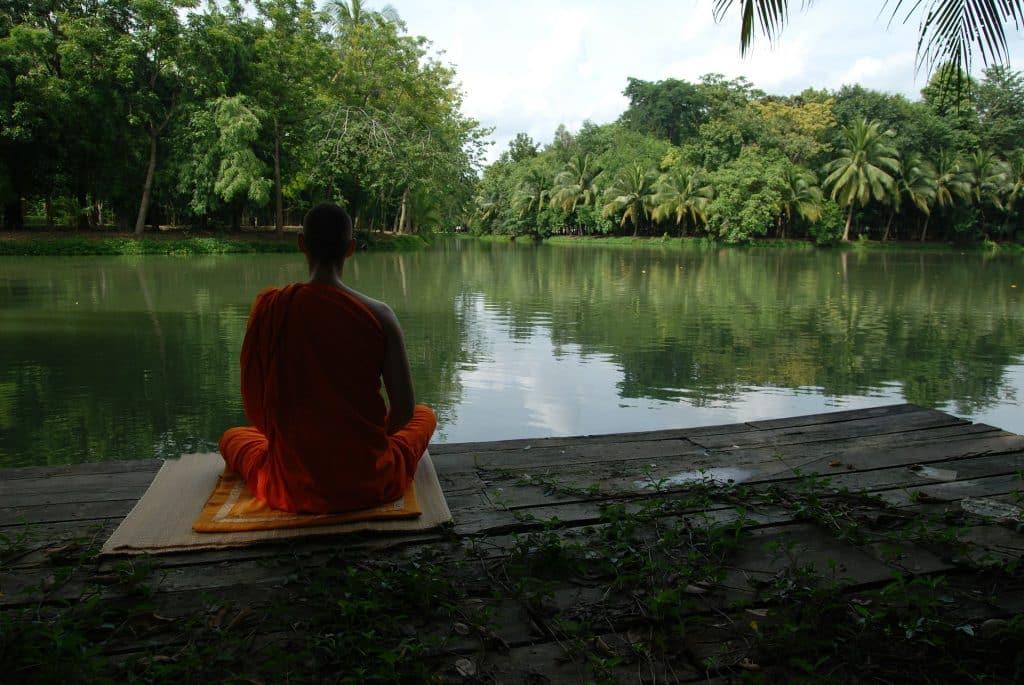 Imagem de um homem sentado de costas sobre um tapete de yoga praticando a meditação em frente a um lago todo arborizado.