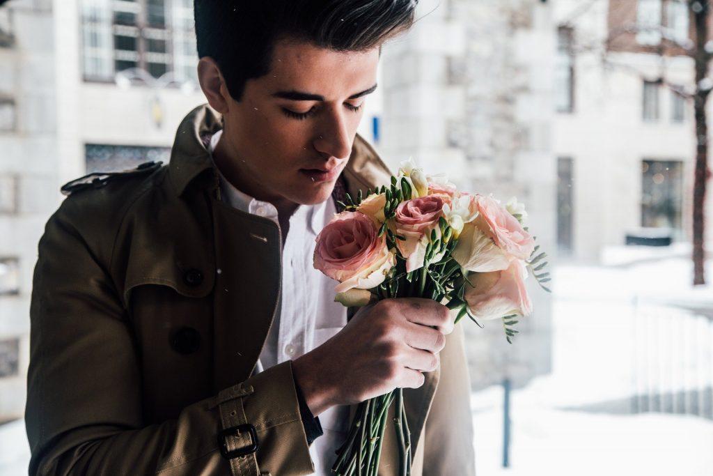 Imagem de um homem no corredor de um prédio. Ele usa uma camisa branca e uma jaqueta na cor marrom. Ele segura em suas mãos um lindo ramalhete de rosas.