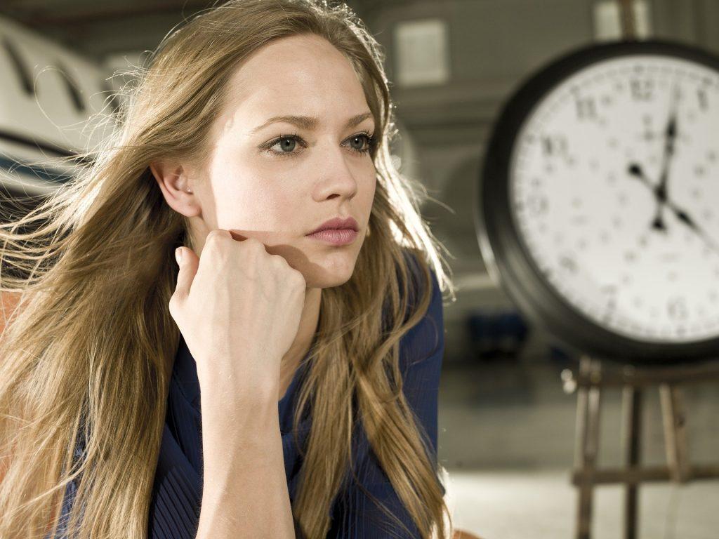 Imagem de uma mulher de cabelos longos e loiros. Ela está com uma das mãos sobre o rosto. Veste uma blusa azul e ao lado dela, um relógio grande marcando as horas.