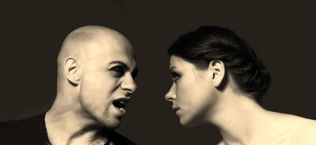 Imagem de fundo preto e em destaque um casal de homem e mulher. Ele está estressado e com um olhar de raiva olhando para a mulher.