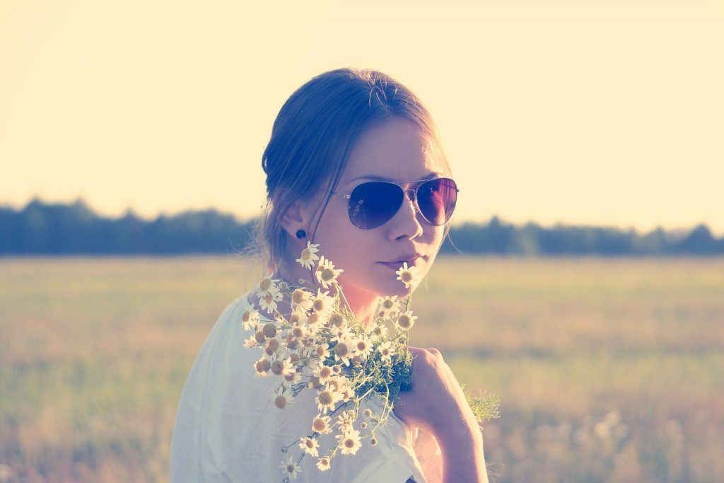 Imagem de uma linda mulher com cabelos longos e presos. Ela está em um campo com uma vegetação alta e verde. Ela usa óculos escuros, veste uma camiseta na cor branca e segura em uma das mãos um ramalhete de margaridas pequenas.