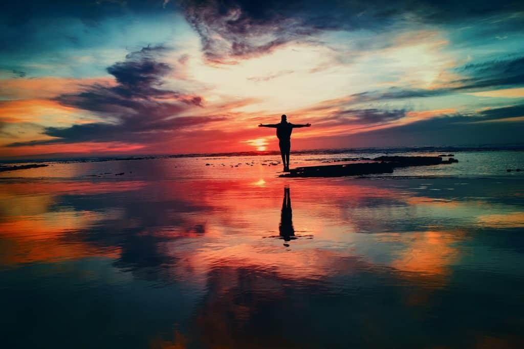 Silhueta de um homem de braços abertos em um local com água que espelha o céu.